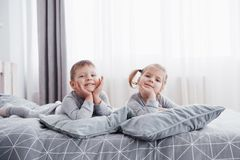 Happy kids playing in white bedroom. Little boy and girl, brother and sister play on the bed wearing pajamas. Nursery. Interior for children. Nightwear and Royalty Free Stock Photos