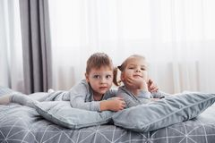 Happy kids playing in white bedroom. Little boy and girl, brother and sister play on the bed wearing pajamas. Nursery. Interior for children. Nightwear and Royalty Free Stock Image