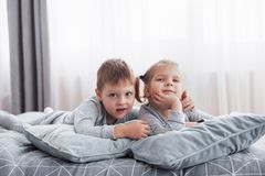 Happy kids playing in white bedroom. Little boy and girl, brother and sister play on the bed wearing pajamas. Nursery. Interior for children. Nightwear and Royalty Free Stock Photography