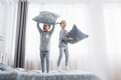 Children in soft warm pajamas playing in bed. Happy kids playing in white bedroom. Little boy and girl, brother and sister play on the bed wearing pajamas Stock Image