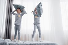Children in soft warm pajamas playing in bed. Happy kids playing in white bedroom. Little boy and girl, brother and sister play on the bed wearing pajamas Stock Images