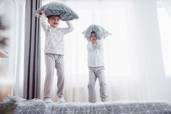 Children in soft warm pajamas playing in bed. Happy kids playing in white bedroom. Little boy and girl, brother and sister play on the bed wearing pajamas Stock Photography