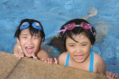 Happy kids in the pool. Kids with goggles playing happily in the pool Royalty Free Stock Photography