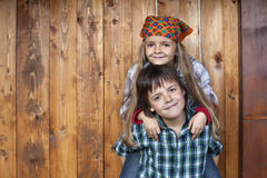 Happy kids portrait against wooden wall Stock Photography