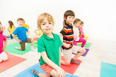 Happy kids practicing gymnastics on mats in gym stock images