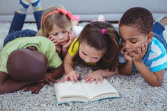 Happy kids reading a book together Stock Image