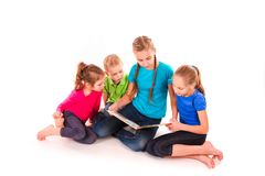 Happy kids reading a book on white. Team work, creativity concept royalty free stock photo