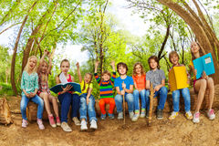 Happy kids reading books outdoor in summer camp. Big group of happy kids, sitting in a row outdoor on the log and reading books in the summer camp Royalty Free Stock Photography