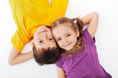 Happy kids relaxing. Laying on white - top view stock photo