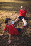 Happy kids relaxing on grass during obstacle course. In boot camp stock photo