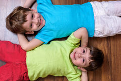 Happy kids relaxing laying on floor- top view Royalty Free Stock Image