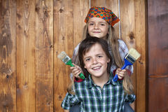 Happy kids repainting the wood shed Stock Photo