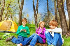 Happy kids resting together sit near yellow tent Royalty Free Stock Photography