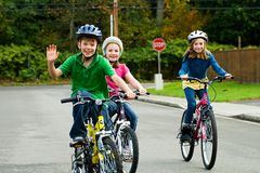 Happy Kids riding bikes. A group of three kids riding bikes on the street. Each child is wearing a helmet for safety stock photography