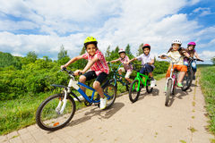 Happy kids riding bikes like in race together Royalty Free Stock Images