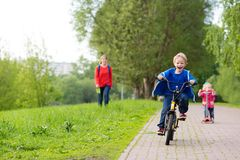 Happy kids riding scooter and bike in the park Royalty Free Stock Photos