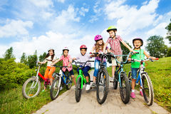 Happy kids in row wear colorful bike helmets. Holding bike handle-bars and are ready to ride their bikes in summer Stock Photo