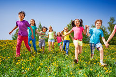 Happy kids run and hold hands in green meadow. During summer Stock Photography