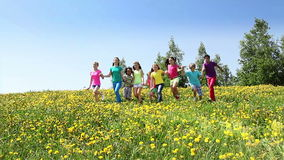 Happy kids run together in dandelion field. Large group of diverse looking children boys and girls running in dandelion yellow field on spring sunny day view stock footage