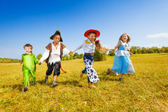 Happy kids run wearing costumes in park Stock Photography