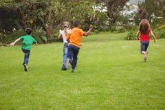 Happy kids running across the grass Stock Photos