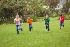Happy kids running across the grass Royalty Free Stock Image