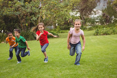 Happy kids running across the grass Stock Images