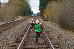 Happy kids running down train tracks. A group of three kids racing outside on train tracks stock photos
