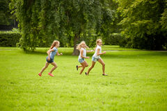 Happy kids running and playing game outdoors. Friendship, childhood, leisure and people concept - group of happy kids or friends playing catch-up game and Royalty Free Stock Image