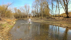 Happy Kids Running in Water. Two happy kids running in a stream, slow motion stock footage