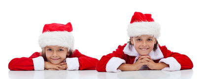 Happy kids in Santa Claus outfit - isolated. Happy kids smiling in Santa Claus outfit - isolated Royalty Free Stock Image