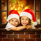Happy kids in Santa hat  look out  window at. Christmas time. With colorful lights from Christmas tree on background. Holidays, christmas, new year, x-mas Stock Image
