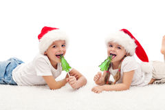 Happy kids with santa hats and candy Royalty Free Stock Photography