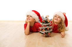 Happy kids with santa hats laying on the floor Stock Photography