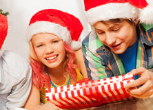 Happy kids in Santa New year hats and with present Stock Images
