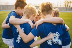 Happy boys in junior football team celebrating success. Happy kids in school sports team. Happy kids in school sports team. Boys gathering and having fun on stock image