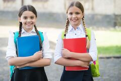 Happy kids in school uniforms hold study books outdoors, development