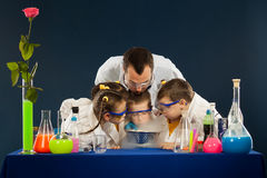 Happy kids with scientist doing science experiments in the laboratory Royalty Free Stock Images