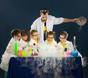 Happy kids with scientist doing science experiments in the laboratory Stock Images