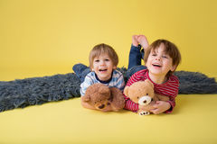 Happy Kids, Siblings, Hugging stuffed toys. Two happy kids, brothers or friends, having fun, playing games, and hugging their stuffed toys royalty free stock images