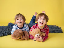 Happy Kids, Siblings, Hugging stuffed toys. Two happy kids, brothers or friends, having fun, playing games, and hugging their stuffed toys royalty free stock photos