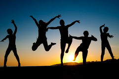 Happy kids silhouettes jumping on the beach Stock Images