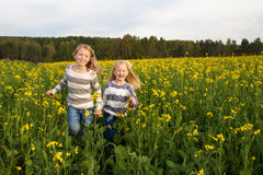 Happy kids  sisters running around laughing  in Royalty Free Stock Photos