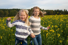 Happy kids  sisters running around laughing  in Stock Photography