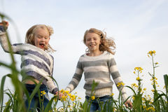 Happy kids  sisters running around laughing  in Stock Image