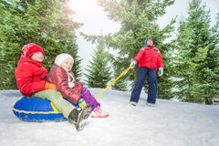 Happy kids sit on snow tube and other pulling them Stock Images
