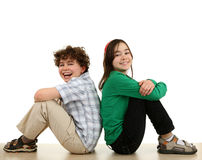 Happy kids sitting. Portrait of two young happy kids isolated on white background stock photography