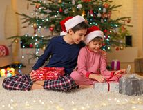 Children under Christmas tree. Happy kids sitting on the floor in front of the Christmas tree Royalty Free Stock Images