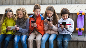 Happy kids sitting with mobile devices. In street royalty free stock photography