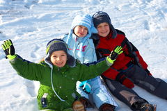 Happy kids sitting in snow. A view of three happy, smiling children sitting together in the winter snow Royalty Free Stock Images